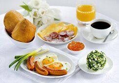 Breakfast with sausage, fried egg, sliced meats and cheese, coffee and jam