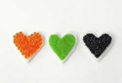 Three heart-shaped canapes with colourful caviar
