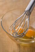 Whisk and egg yolk in a glass mixing bowl