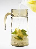 Filling a carafe with essence of lemonade