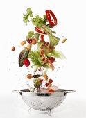Salad ingredients being washed in a colander