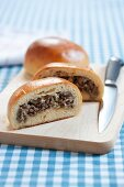 Runzas (Baked Bread Pocket Filled with Meat); Halved on Cutting Board