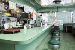 An old man sitting in a diner