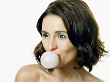 A young woman blowing a bubble with chewing gum
