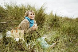 A woman on a sand dune with a hot drink