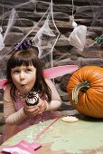 Mädchen mit einem Spinnen Cupcake