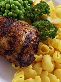 Barbecued chicken breast with noodles and peas