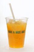 Orange juice in plastic tumbler with straw