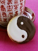 A Yin Yang biscuit beside a Chinese cup