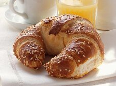 Croissant with sesame; grapefruit juice; coffee cup