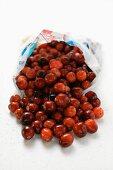 Fresh cranberries falling out of plastic bag