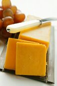 Extra Sharp Cheddar with cheese knife and grapes