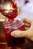 Pouring strawberry jam into jar
