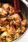 Braised chicken with onions in cast-iron frying pan