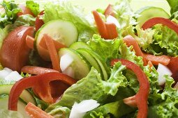 Salad leaves with cucumber, tomato, carrots, peppers (close-up)