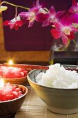 Bowl of rice beside burning candles (Thailand)