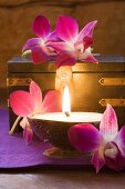 Thai table decoration: candles, orchids, wooden box