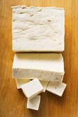 Tofu, a block, a slice and diced on wooden background