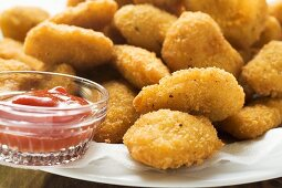 Many chicken nuggets with ketchup on plate
