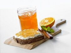 Orange jelly on bread and in jar
