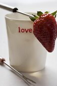 Beaker with the word 'love' and fondue fork with strawberry