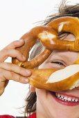 Boy looking through a pretzel