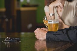 Man and woman at a bar with beer and wine, car keys