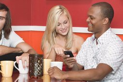 Young people with mobile phone at table in a café or restaurant