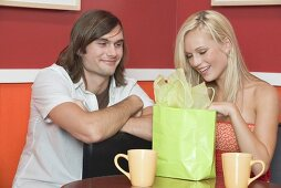 Girl in café opening present from young man