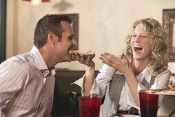 Frau füttert Mann mit Pizza im Restaurant