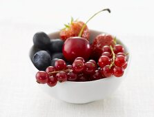 Berries and one cherry in white china bowl