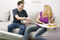 Young couple with pizza & football sitting in front of TV