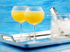Citrus fruit cocktail and ice cube container on tray