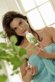 Woman smelling herbal body lotion