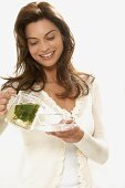 Woman pouring herself a cup of mint tea