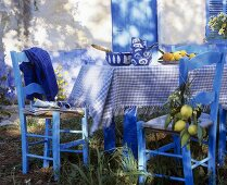 Table with blue and white tablecloth, crockery and lemons