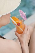 Woman drinking Planter's Punch by pool