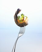 Prawn with parsley and sliver of carrot on a fork