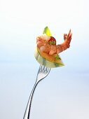 A piece of melon and a cooked prawn on a fork
