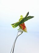 Charentais melon, chilli and green asparagus on a fork