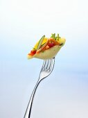 Pasta shell filled with vegetables on a fork