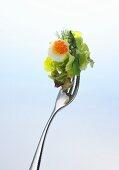 Lettuce, asparagus, quail's egg and red caviar on a fork