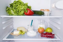 An open fridge with various types of fresh produce