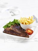 T-bone steak with chips and grilled tomatoes