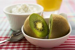 Halved kiwi fruit in front of a small bowl of cottage cheese