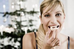 Young woman biting into biscuit