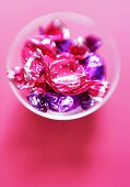 Sweets in pink and purple wrappers in a small bowl