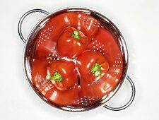 Three red peppers in a colander