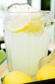 Lemonade in a glass jug with slices of lemon
