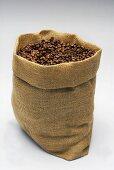 A jute sack full of roasted coffee beans